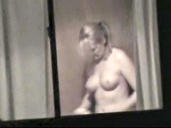 Topless bimbo is kinkily voyeured through the window