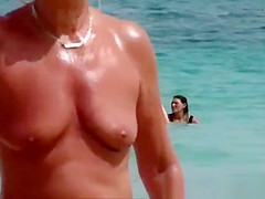 The old woman is walking topless on the beach