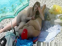 Nudist blowjob under sun umbrella