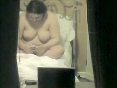 Fat sister with large breasts texts her friend while completely naked