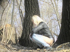 Irresistible girl holds onto jeans while piddling in the city park