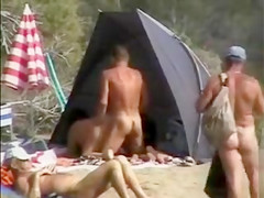 Mature nudists copulating for an audience on the nude beach