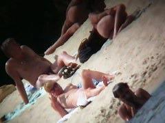 A voyeur is hunting for beautiful women on a nudist beach