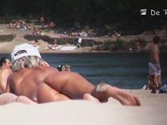 Beach nudist girl talks on phone and gets voyeured