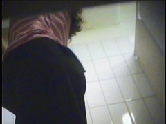 A milf is putting on a yellow striped bikini in the swimming pool changing room