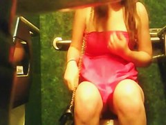 The luxurious gal in the pink dress is pissing in the toilet
