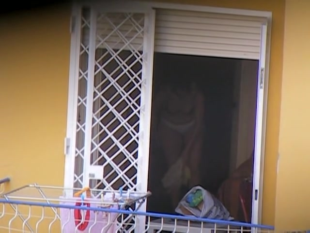 Real neighbor taking off her brassier at the open window