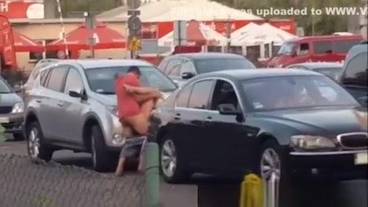 Boy with girl having sex on a car in the bazaar.