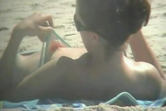 The downblouse girl becomes an object of a hidden spy cam on the beach